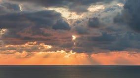 Las nubes que cruzan el cielo sobre el horizonte de mar en la puesta del sol con los rayos del sol emergen a través de las nubes  almacen de metraje de vídeo