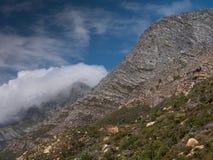 Las nubes que se encrespan sobre la montaña rematan a lo largo de la costa de Western Cape en Suráfrica fotografía de archivo