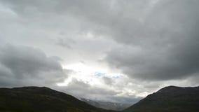 Las nubes que se mueven sobre pico de montaña majestuoso con nieve remiendan el timelapse almacen de metraje de vídeo