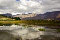 Las nubes reflejan en el lago claro de la montaña en África Fotografía de archivo libre de regalías