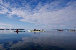 Las nubes reflejaron en el océano vidrioso como los kayakers se baten en las islas externas de la selva tropical de la Osa Mayor  foto de archivo