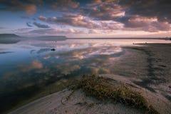 Las nubes rosadas y azules en la puesta del sol reflejaron en agua inmóvil fotos de archivo libres de regalías