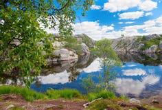 Las nubes se reflejan en el pequeño lago entre piedras enormes en Fotos de archivo