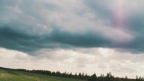 Las nubes tormentosas azul marino a cámara lenta sobre prado surraunded el bosque antes de lluvia almacen de metraje de vídeo