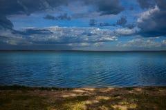 Las nubes y el sol irradia sobre el lago en la salida del sol foto de archivo libre de regalías