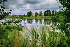 Las nubes y las reflexiones de tormenta oscuras en el lago riegan la superficie Fotografía de archivo