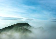 Las nubes y se empañan en la montaña fotos de archivo