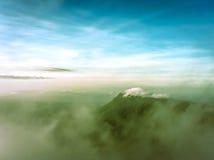 Las nubes y se empañan en la montaña imagenes de archivo