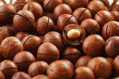 Las nueces de macadamia en grandes cantidades en bulto bajo la forma de textura de la fruta natural fresca descascaron una nuez e fotos de archivo libres de regalías