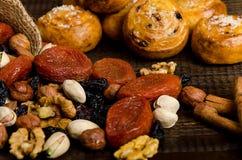 Las nueces, las frutas secadas, los pistachos y las galletas hechas en casa se dispersan del bolso en la tabla fotos de archivo libres de regalías