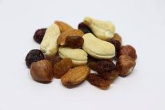 Las nueces mezcladas con las pasas están en el fondo blanco - Colección sana de las comidas foto de archivo libre de regalías