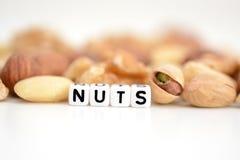 """Las nueces mezcladas crudas y el  del """"nuts†de la palabra deletreado por las gotas tejadas de la letra se separaron en una t Foto de archivo libre de regalías"""