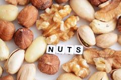 """Las nueces mezcladas crudas y el  del """"nuts†de la palabra deletreado por las gotas tejadas de la letra se separaron en una t Imagen de archivo libre de regalías"""