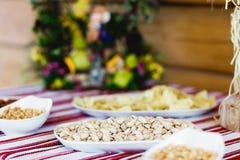 Las nueces mienten en diversas placas blancas en la comida fría Imagenes de archivo