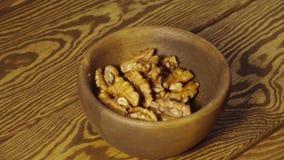 Las nueces peladas caen en la taza de madera - cámara lenta metrajes