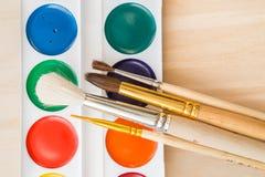 Las nuevas acuarelas y limpian cepillos Fotografía de archivo libre de regalías
