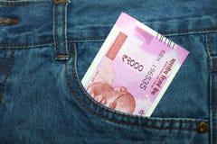 Las nuevas 2000 notas de la rupia en un indio sirven el bolsillo delantero de la mezclilla Fotos de archivo libres de regalías