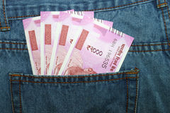 Las nuevas 2000 notas de la rupia en un indio sirven el bolsillo trasero de la mezclilla Fotos de archivo libres de regalías