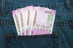 Las nuevas 2000 notas de la rupia en un indio sirven el bolsillo trasero de la mezclilla Fotografía de archivo libre de regalías