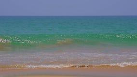Las olas oceánicas azules son incidente en la playa arenosa almacen de metraje de vídeo