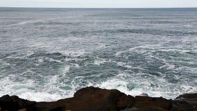 Las olas oceánicas de la cámara lenta con la roca de la lava apuntalan la bahía Oregon de Depoe almacen de video