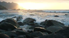 Las olas oce?nicas se estrellan en rocas y espray en luz hermosa de la puesta del sol en la playa de Benijo en Tenerife, islas Ca almacen de video