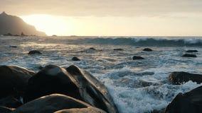 Las olas oce?nicas se estrellan en rocas y espray en luz hermosa de la puesta del sol en la playa de Benijo en Tenerife, islas Ca almacen de metraje de vídeo