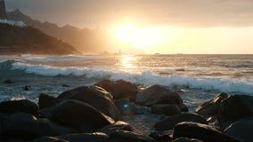 Las olas oce?nicas se estrellan en rocas y espray en luz hermosa de la puesta del sol en la playa de Benijo en Tenerife, islas Ca metrajes
