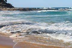 Las ondas acometen sobre orilla sobre rocas volcánicas planas con más rocas que penetran hacia fuera en el mar imágenes de archivo libres de regalías