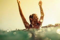 Las ondas atractivas del mar de la nadada de la muchacha del bikini salpican tono del vintage fotografía de archivo