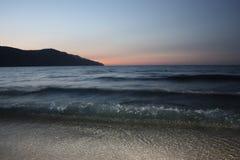 Las ondas azul marino del mar sobre ligero enarenan con la montaña y la puesta del sol en horizonte Fotografía de archivo libre de regalías