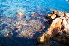 Las ondas azules se rompen en las rocas de la orilla imagenes de archivo