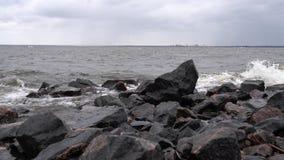 Las ondas batieron contra las rocas en la orilla del mar almacen de video