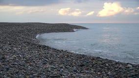 Las ondas batieron en la costa costa con una puesta del sol hermosa almacen de video