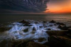 Las ondas batieron en la playa en la puesta del sol Imágenes de archivo libres de regalías