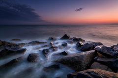 Las ondas batieron en la playa en la puesta del sol Foto de archivo libre de regalías
