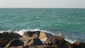 Las ondas coloridas asombrosas del mar están lavando piedras grandes en un rompeolas en día soleado metrajes