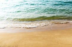 Las ondas de la playa golpearon la playa por la tarde Fotos de archivo