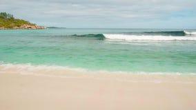 Las ondas de la visión se rompen en la playa de la isla en la puesta del sol Las ondas del mar en los Cocos hermosos de Anse de l almacen de metraje de vídeo