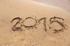 Las ondas de las playas y mandan un SMS a 2015 exhaustos en la arena Imagen de archivo libre de regalías