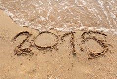 Las ondas de las playas y mandan un SMS a 2015 exhaustos en la arena Imagenes de archivo