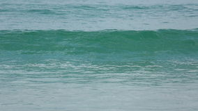 Las ondas del azul rodaron en la arena de la playa de Karon