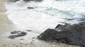 Las ondas del mar de la cámara lenta explotan la playa a lo largo de orillas de la playa La erosión de la agua de mar se relaja y metrajes