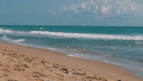 Las ondas del mar están rodando en una playa de la arena