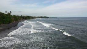 Las ondas del mar ruedan en la costa pedregosa, Bali, Indonesia almacen de video
