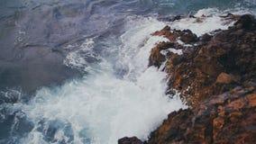 Las ondas del mar se estrellan contra la roca en la cámara lenta