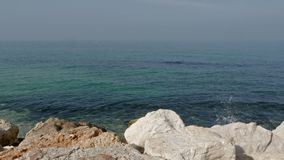 Las ondas del mar se rompen contra una piedra en la orilla