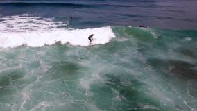 Las ondas espumosas blancas enormes que se estrellan en agua azul profunda del océano como persona que practica surf profesional  almacen de metraje de vídeo