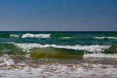 Las ondas grandes del mar rodaron en la arena imagenes de archivo