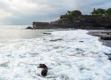 Las ondas grandes en Tanah sortean el acantilado en Bali, Indonesia imagenes de archivo